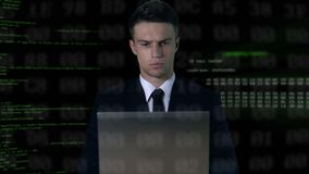 Man in suit typing on laptop, software code on background, password hack. Stock footage stock footage