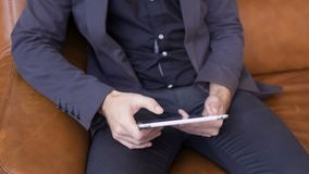 Man in suit uses digital tablet. Handsome man uses his tablet sitting on sofa. The businessman wearing suit is relaxing and looking the news in the internet stock video footage