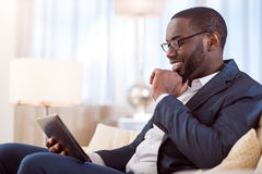 Man in suit using tablet. Some relaxation. Handsome confident afro American man using a tablet while sitting on the sofa and touching his chin Stock Photos