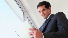 Man in suit using a touchpad. Near a window stock video