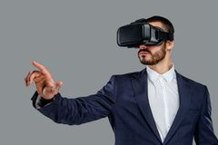 A man in a suit with virtual reality glasses on his head. Portrait of bearded male in a suit with virtual reality glasses on his head isolated on grey Royalty Free Stock Images