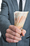 Man in suit with a wad of euro bills Stock Image