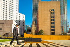 Man in suit walking in a business park. A young man in a suit with a red tie and hat walking Royalty Free Stock Photo