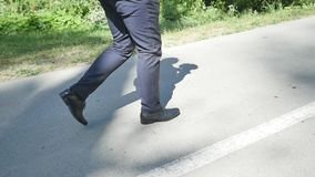 Man in suit walking on the road slowmo stock video