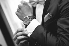 Man with suit and watch on hand. Close up of elegant man in suit with watch on hand royalty free stock photography