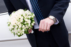 A man in suit with watch handsand a flower bouquet Royalty Free Stock Image