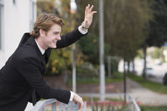 Man in suit waving at someone Stock Photography