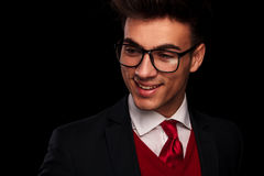 Man in suit, wearing tie and glasses. Close portrait of attractive young man in suit, wearing tie and glasses, looking away from the camera in dark studio Royalty Free Stock Photos