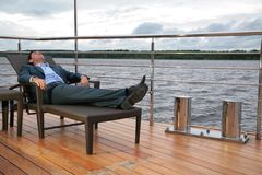 Man in suit, who rests in chaise lounge on  wharf Royalty Free Stock Image