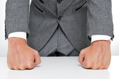 Man in suit. Withs his fists on the desk Royalty Free Stock Photos