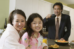 Man in suit with woman and girl in foreground at kitchen Stock Photography