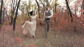 A loving couple running around in an autumn park holding hands, slow motion shooting. A man in a suit and a woman in a white dress are running slowly among the stock video