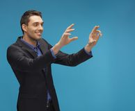 Man in suit working with something imaginary Royalty Free Stock Images