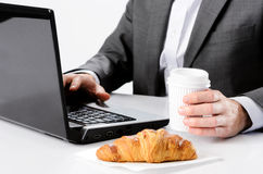 Man in suit works  while having breakfast Royalty Free Stock Photography