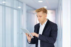 A man in  suit works with the tablet  office corridor Royalty Free Stock Photo
