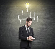 Man in suit writing, light bulb with questions Stock Photography