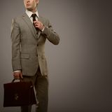 Man with suitcase. Businessman with a briefcase isolated on grey Stock Photo