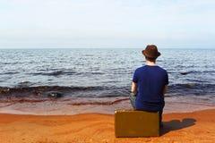 The man with a suitcase on a beach Stock Photos