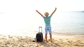 Man with suitcase on the beach. Summer travel and vacation concept.  stock video