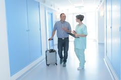 Man with suitcase being admitted to hospital by nurse. Man stock image