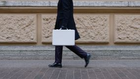 Man with suitcase in city. Side view of man in black going in city with suitcase stock footage