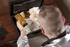 Man with suitcase full of money and gold. The suitcase standing on a table, the face is not visible royalty free stock image