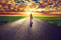 Man with suitcase and hat on long straight road. Towards sunset sky. Travel, business, destination, adventure concepts Royalty Free Stock Photos