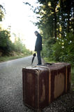 Man with suitcase hitchhiking in a rural road. A man with suitcase and umbrella hitchhiking in a rural road Stock Photo