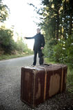 Man with suitcase hitchhiking in a rural road. A man with suitcase and umbrella hitchhiking in a rural road Royalty Free Stock Photography