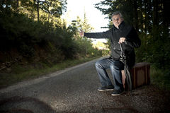 Man with suitcase hitchhiking in a rural road. A man with suitcase and umbrella hitchhiking in a rural road Royalty Free Stock Photo