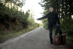 Man with suitcase hitchhiking in a rural road Stock Photo