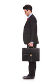 Man with suitcase looks down Royalty Free Stock Photography