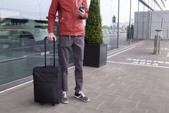 A man with suitcase and mobile phone near of airport. royalty free stock photo