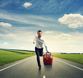 Man with suitcase running on the road Royalty Free Stock Images
