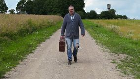 Man with suitcase on rural road. In summer day stock video