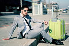 Man with suitcase sitting in the street. Man dressed in suit and suitcase sitting on the floor in the street Stock Image