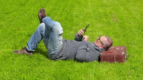 Man with suitcase sleeping on grass and using tablet PC. In summer day stock footage