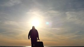 Man with suitcase slow motion to opening sea view silhouette. Conceptual stock video