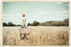 Man with suitcase standing on field in vintage Royalty Free Stock Images