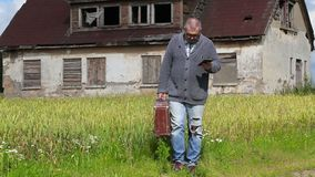 Man with suitcase take pictures on tablet PC near abandoned building. In summer day stock footage
