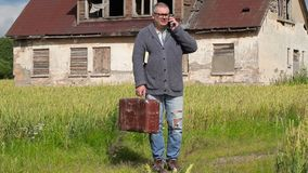 Man with suitcase talking on smart phone near abandoned building. In summer day stock video footage