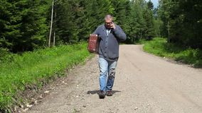 Man with suitcase talking on smart phone and walking. In summer day stock footage