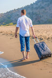 Man with a suitcase walking. Along the beach Royalty Free Stock Photography