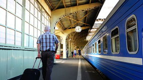 A man with a suitcase walking along the platform of the train station along the passenger stock footage