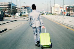 Man with suitcase walking along the street. Man dressed in suit and suitcase in the street Royalty Free Stock Photo