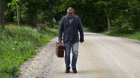 Man with suitcase walking and try stop the car. In summer day stock video footage