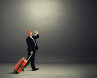 Man with suitcase waving hand Royalty Free Stock Photo