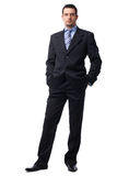 Man In Suite. Portrait of a confident young  businessman with hands in pockets on white background Royalty Free Stock Photos