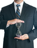 Man in suite holding hourglass Royalty Free Stock Photo
