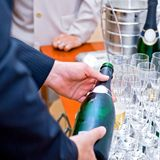 Man in suite pouring champagne to glasses Royalty Free Stock Images